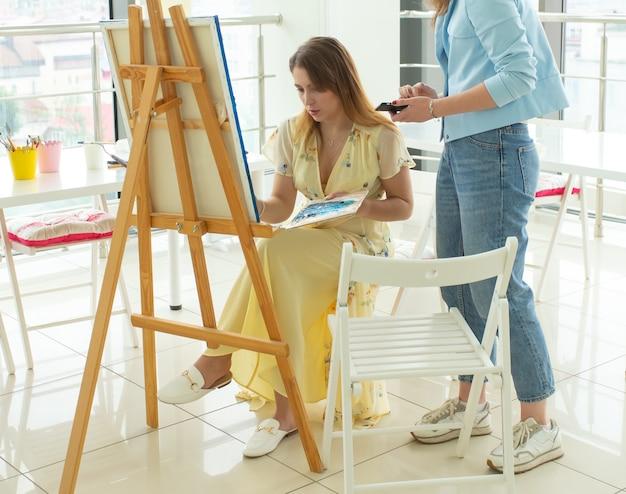 Concept de cours d'art, de dessin et de créativité - gros plan sur une étudiante assise devant un chevalet avec palette et pinceau. le professeur l'aide