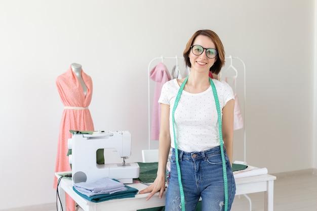 Concept de couturière, créateur de mode, tailleur et personnes - belle créatrice de mode debout en studio