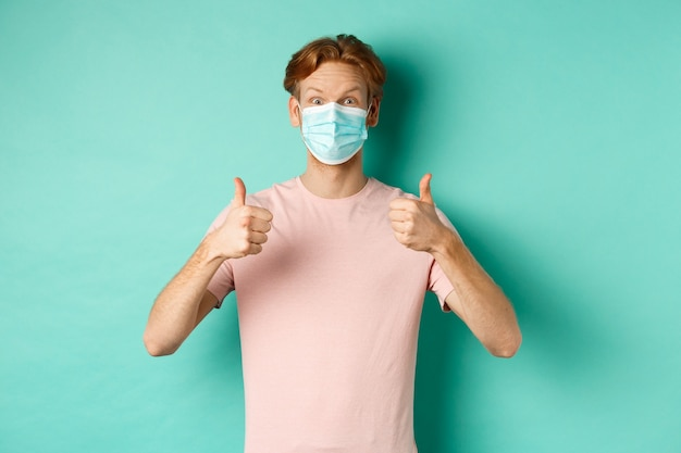 Concept de covid-19, de pandémie et de mode de vie. gai gars rousse dans un masque médical montrant les pouces vers le haut en approbation, comme et loue le produit, debout sur fond turquoise