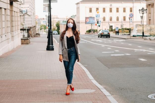 Concept de covid-19 et de pollution atmosphérique pm2.5. pandémie, portrait d'une jeune femme portant un masque de protection dans la rue. concept santé et sécurité.