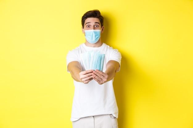 Concept de covid-19, quarantaine et mesures préventives. jeune homme caucasien donnant des masques médicaux pour vous, debout sur fond jaune.
