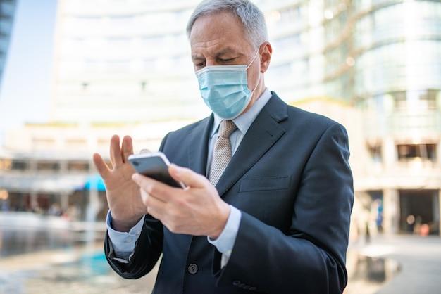 Concept de covid, homme d'affaires âgé masqué utilisant son smartphone en plein air