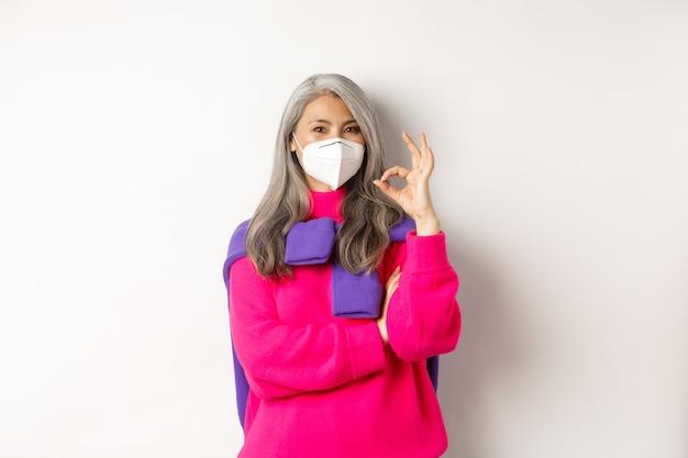 Concept de covid, de pandémie et de distanciation sociale. femme âgée asiatique gaie et élégante portant un respirateur du coronavirus, montrant le signe ok, debout sur fond blanc.
