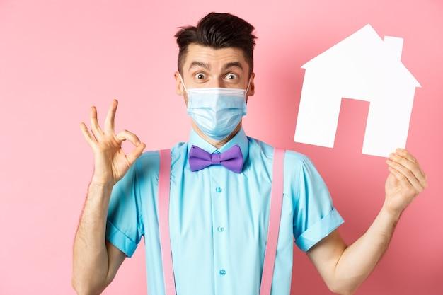 Concept de covid, pandémie et immobilier. excité jeune homme en masque médical montrant le signe ok et la découpe de la maison en papier, recommandant l'agence, debout sur fond rose.