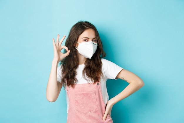 Concept de covid, de santé et de pandémie. très bon. jeune femme de soutien portant un respirateur médical et montrant son approbation, louange portant des masques faciaux en public, fond bleu