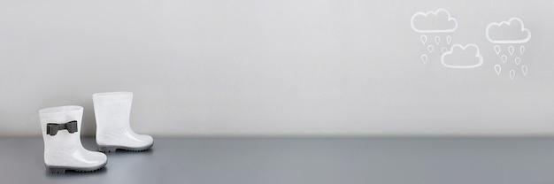 Concept créatif d'automne. bannière faite avec des bottes de pluie en caoutchouc blanc brillant avec des arcs et des nuages de pluie peints sur fond gris. espace de copie.