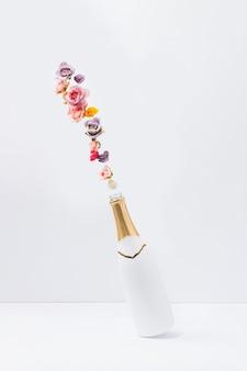 Concept créatif avec bouteille de champagne blanc et fleurs printanières naturelles colorées