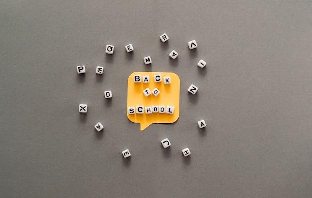Concept créatif d'éducation scolaire à plat avec autocollants, lettrage de retour à l'école et lettres sur fond gris. espace de copie. modèle de texte ou de conception