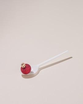 Concept créatif réalisé avec une cuillère blanche et une décoration de noël