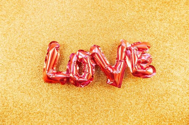 Concept créatif de la saint-valentin. ballon gonflable en aluminium brillant rose en forme de mot amour fond doré. vue de dessus à plat avec espace de copie. vacances, célébration, décoration de fête de mariage bachelorette