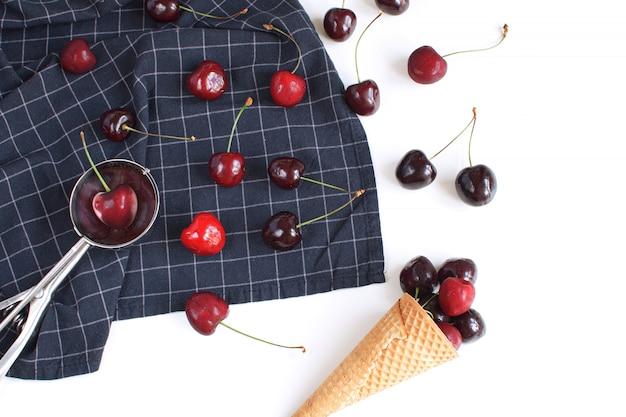 Concept de crème glacée cerises fraîches et cornet de gaufres sur une serviette à carreaux