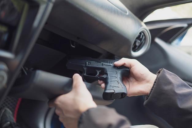 Un concept de crime, un cambrioleur prenant le pistolet et planifiant un meurtre