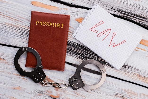 Concept de crime international à plat. passeport avec menottes sur la vue de dessus de table en bois blanc.
