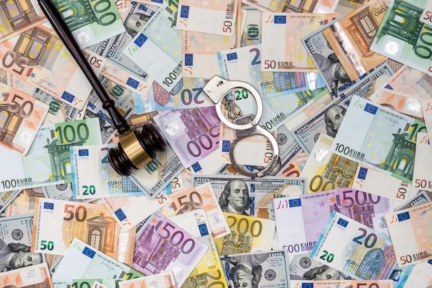 Concept de crime - menottes marteau dollars et billets en euros