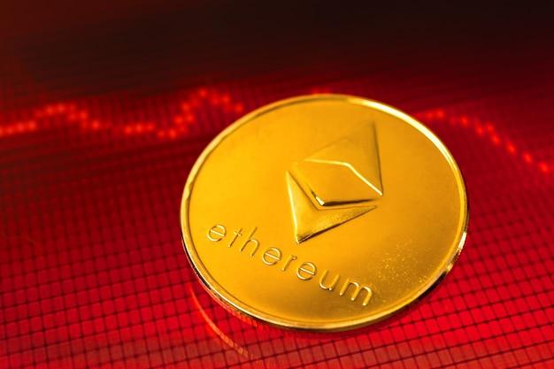 Concept de crise de crypto-monnaie ethereum, le coût de la pièce crypto est en baisse, graphiques boursiers rouges avec des flèches sur la photo d'arrière-plan