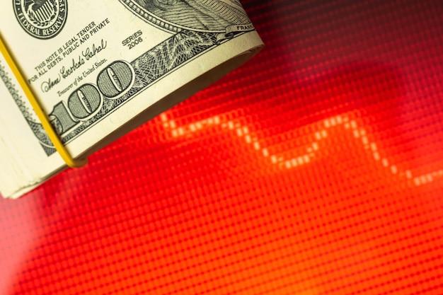 Concept de crise économique et mondiale, billets de banque en dollars américains de l'argent américain sur des graphiques boursiers rouges en arrière-plan, photo de l'espace de copie