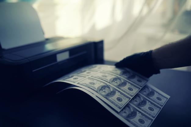 Le concept de la crise économique mondiale. production illégale de dollars américains. imprimez de l'argent sous terre. impression de billets de cent dollars par un criminel.