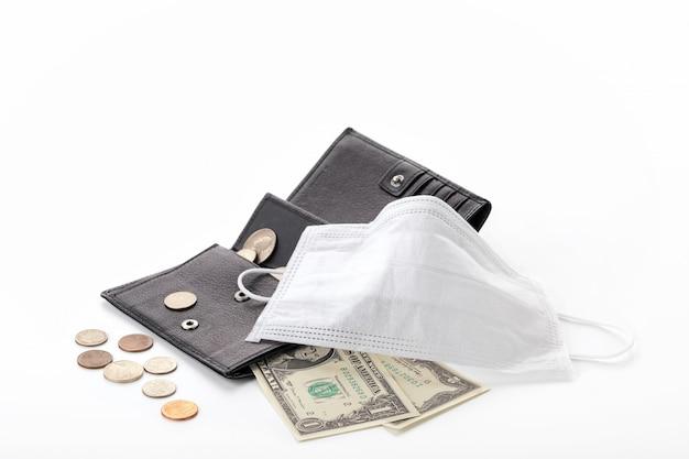 Concept d'une crise mondiale et d'une baisse des revenus due au pandémie de coronavirus covid-19. portefeuille avec un dollar, des cents et un masque de protection isolé.