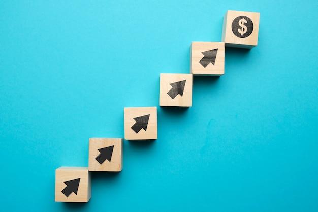 Concept de croissance du dollar américain et avec des icônes sur des blocs de bois.