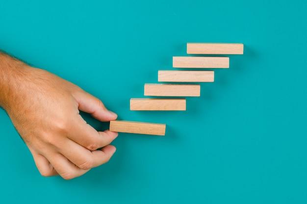 Concept de croissance d'entreprise sur table turquoise à plat. main empiler des blocs de bois.