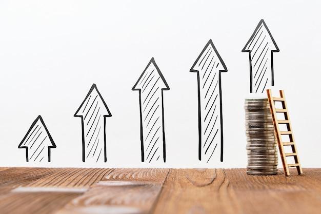 Concept de croissance et de revenu de l'entreprise avec des flèches dessinées et des pièces avec échelle.