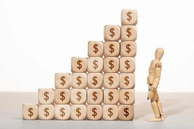 Concept de croissance, de richesse ou de richesse. mannequin en bois à la recherche d'un groupe de blocs en bois empilés avec symbole dollar