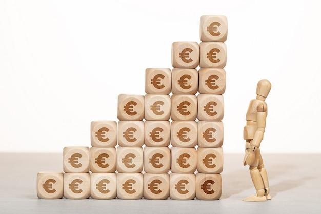 Concept de croissance, de richesse ou de richesse. mannequin en bois à la recherche d'un groupe de blocs en bois empilés avec le symbole de l'euro