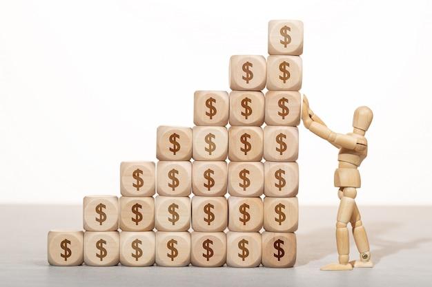 Concept de croissance, de richesse ou de richesse. mannequin en bois tenant une pile de blocs en bois empilés avec symbole dollar