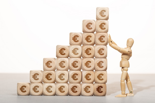 Concept de croissance, de richesse ou de richesse. mannequin en bois tenant une pile de blocs en bois empilés avec le symbole de l'euro
