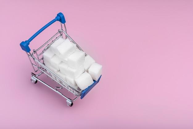 Concept de cubes de sucre. cubes de sucre blanc dans le panier sur le rose. copier l'espace pour le texte.