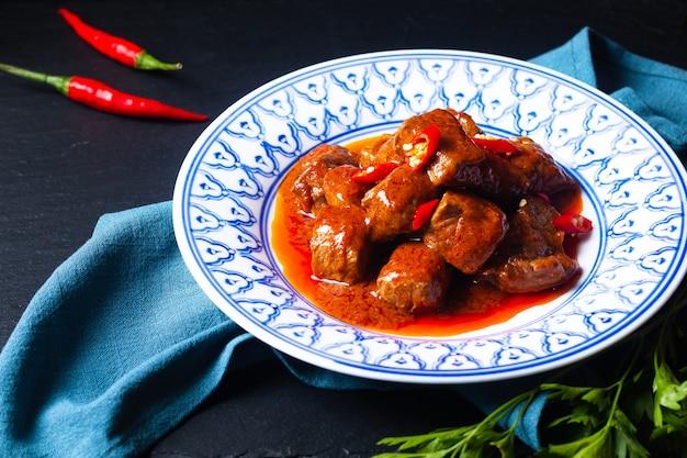 Concept de cuisine asiatique sambal goreng daging beef au curry rouge chili et pâte d'épices sur fond noir avec copie espace