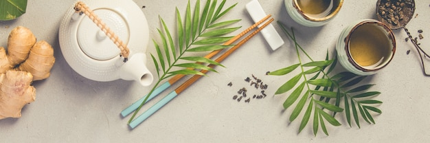 Concept de cuisine asiatique - thé et baguettes sur un fond de béton gris