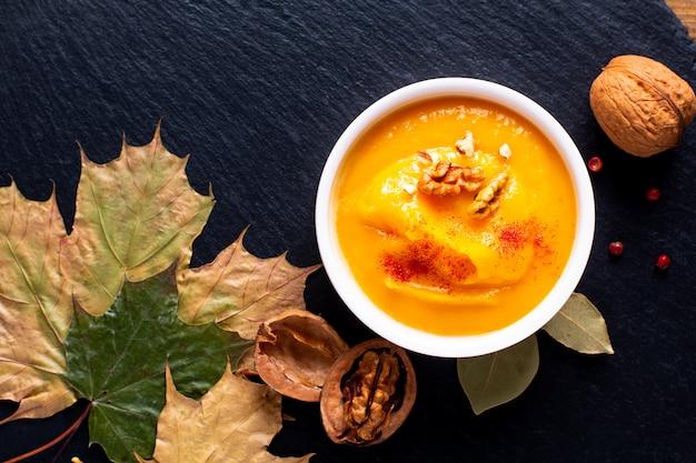 Concept de cuisine automne-hiver soupe de potiron ou de noyer cendré sur une plaque de pierre ardoise noire
