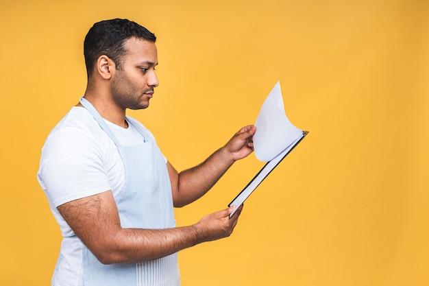 Concept de cuisine, de cuisine et de personnes - chef masculin indien afro-américain avec presse-papiers isolé sur fond jaune.