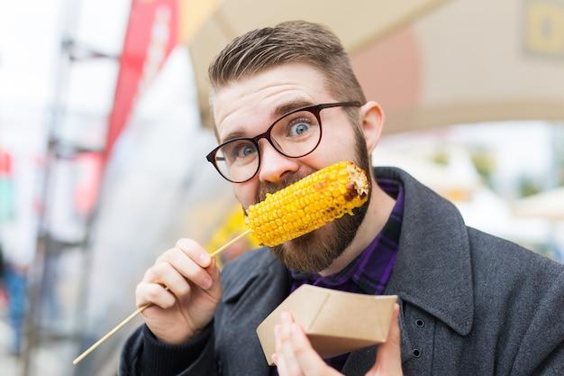 Concept de cuisine et de cuisine de rue - homme mangeant du maïs grillé. la nourriture végétarienne. légumes sains et savoureux.