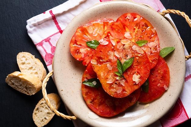 Concept de cuisine d'été salade de tomates anciennes sur fond noir avec espace de copie