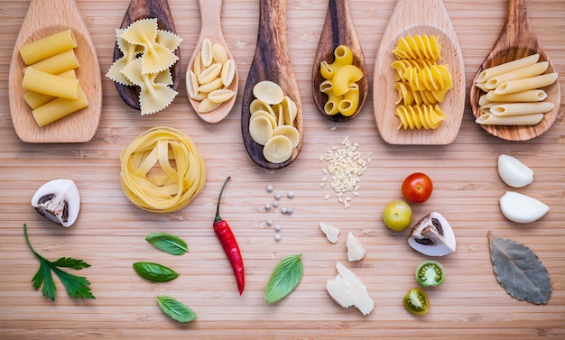 Concept de cuisine italienne. différentes sortes de pâtes avec des ingrédients sur une planche à découper en bambou.