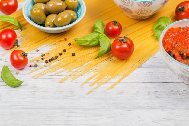 Concept de cuisine italienne. ingrédients pour la préparation des spaghettis de pâtes - tomate, huile d'olive, épices, herbes, olives vertes, sauce tomate, fond en bois blanc. vue de dessus avec espace de copie pour le texte
