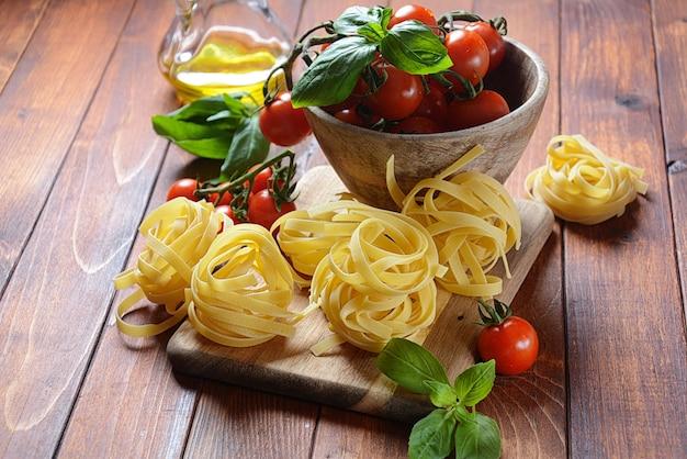 Concept de cuisine italienne avec des pâtes crues, tomate, basilic et huile