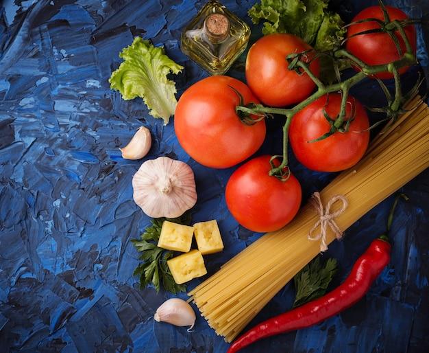 Concept de cuisine italienne. pâtes, tomates, huile d'olive, poivrons, persil et fromage. mise au point sélective. haut