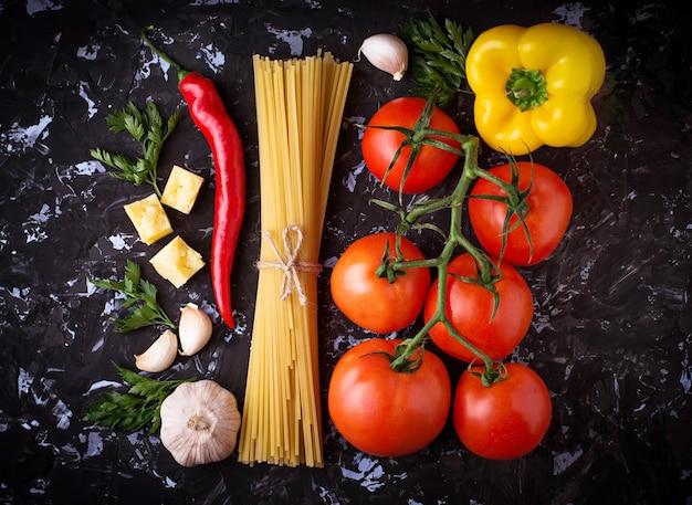 Concept de cuisine italienne. pâtes, tomates, huile d'olive, poivrons, persil et fromage. mise au point sélective.