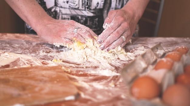 Concept de cuisine et de maison - gros plan sur des mains féminines pétrissant la pâte à la maison. flou artistique