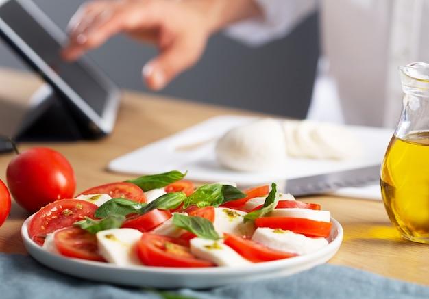 Concept de cuisine maison. homme à la recherche d'informations sur internet comment faire cuire la salade caprese, est une salade italienne célèbre avec des tomates fraîches, du fromage mozzarella et du basilic