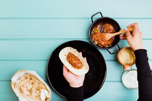 Concept de cuisine mexicaine avec les mains préparant le burrito