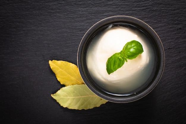 Concept de cuisine mozzarell biologique dans une tasse en céramique avec basilic et feuilles de laurier