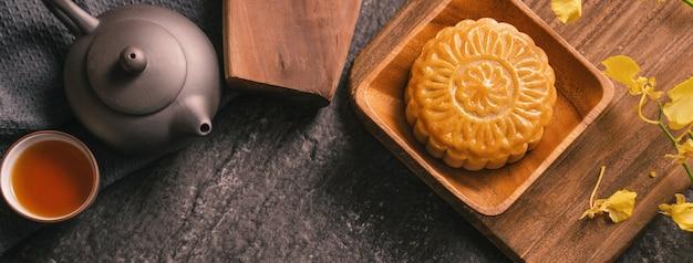 Concept de cuisine traditionnelle du festival de la mi-automne - beau gâteau de lune sur une table en ardoise noire avec thé, moule à pâtisserie, fleur, vue de dessus, mise à plat, espace de copie