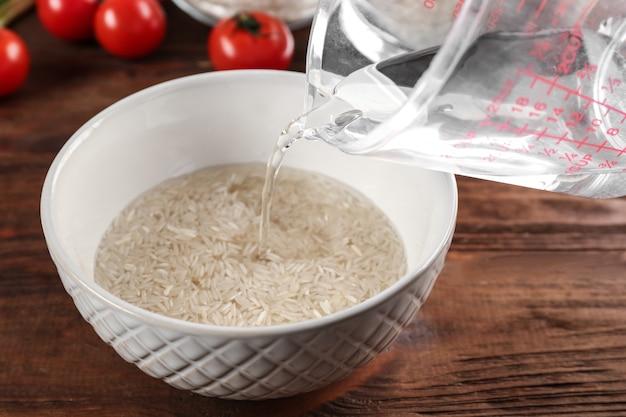 Concept de cuisine. verser de l'eau dans un bol avec du riz