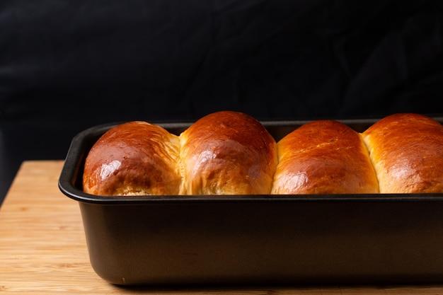 Concept de cuisson alimentaire pain cuit au four bio fait maison frais dans une poêle à pain sur une planche en bois avec espace de copie