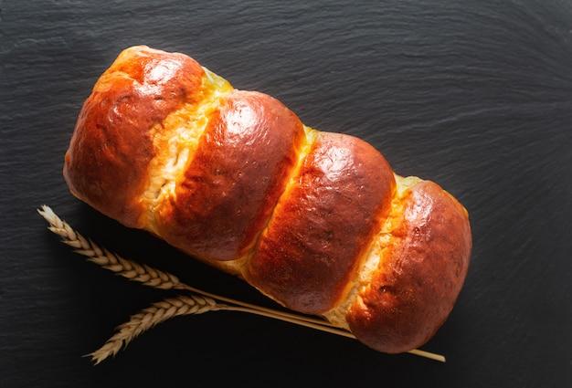 Concept de cuisson des aliments pain de pain au lait doux fait maison bio au four en pain sur ardoise noire avec copie espace