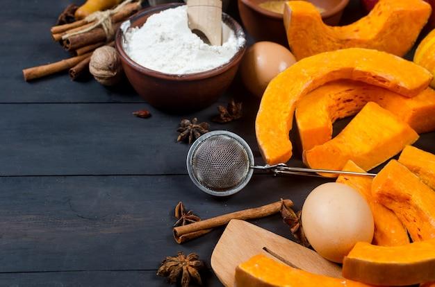 Concept de cuisson d'automne. cadre avec citrouille, pomme, noix, cannelle, oeuf et farine sur la table en bois. cuisson du processus de cuisson avec des ingrédients. vue de dessus. espace de copie,